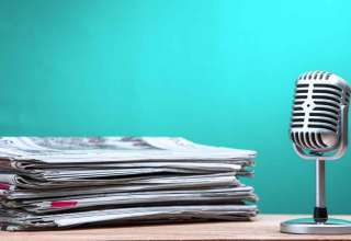 Retro microphone with newspaper on wooden table
