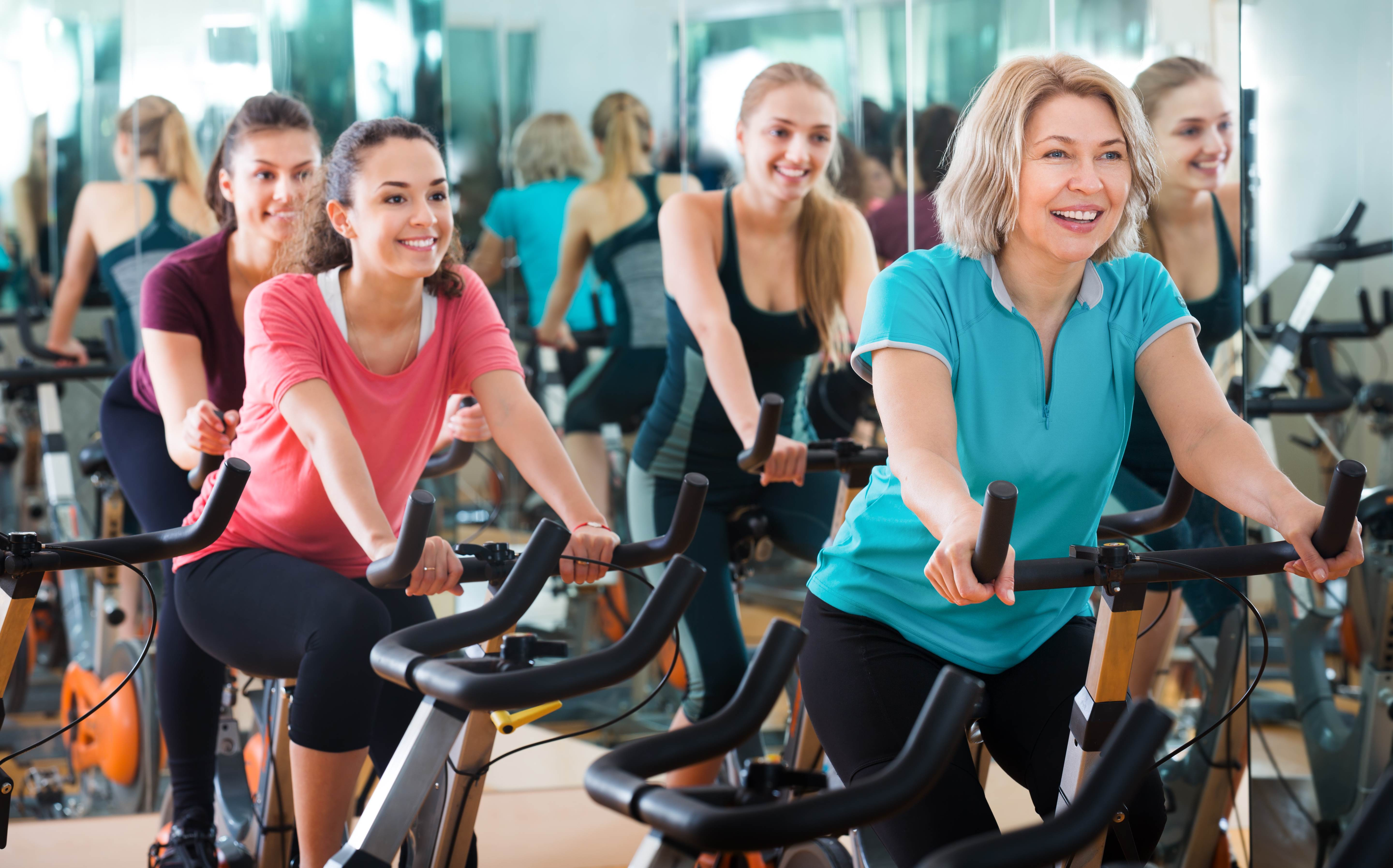 Positive Females Of Different Age Training On Exercise Bikes Wallpaper