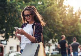 Young woman texting while enjoying a day shopping Wallpaper