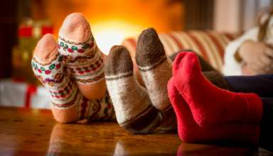 Close-up photo of family feet in wool socks at fireplace