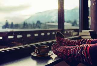 Feet in woollen socks by the Alps mountains view