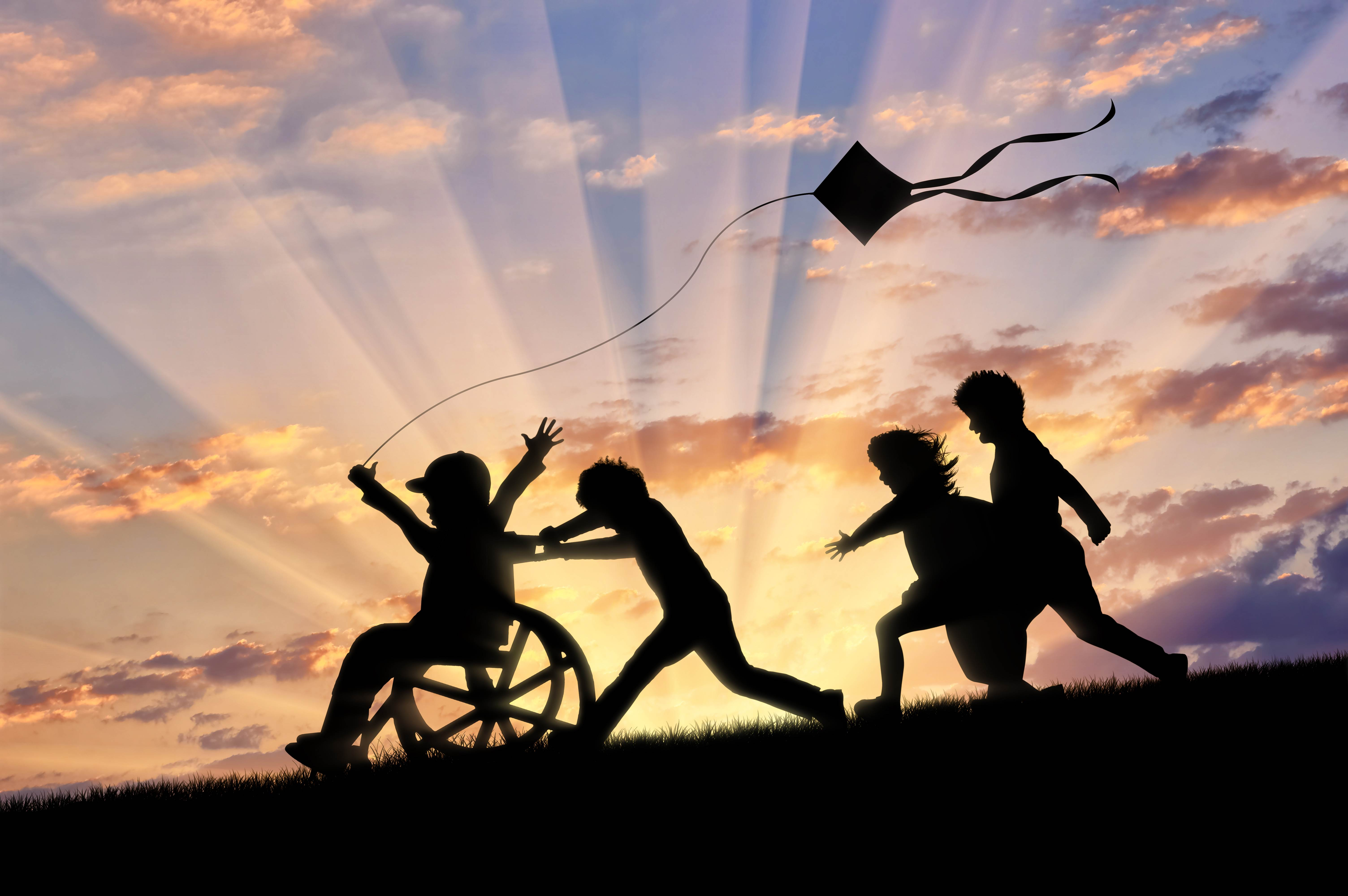 Happy boy in wheelchair playing with children and kite sunset