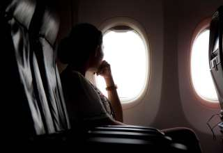 Silhouette of woman looks out the window of an flying airplane