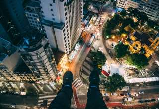 Man Sitting on High Rise Building Taking Photo Below Wallpaper