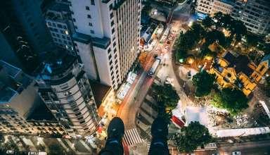 Man Sitting on High Rise Building Taking Photo Below Wallpaper