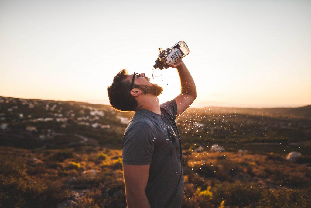 Man drinking water from water bottle Wallpaper