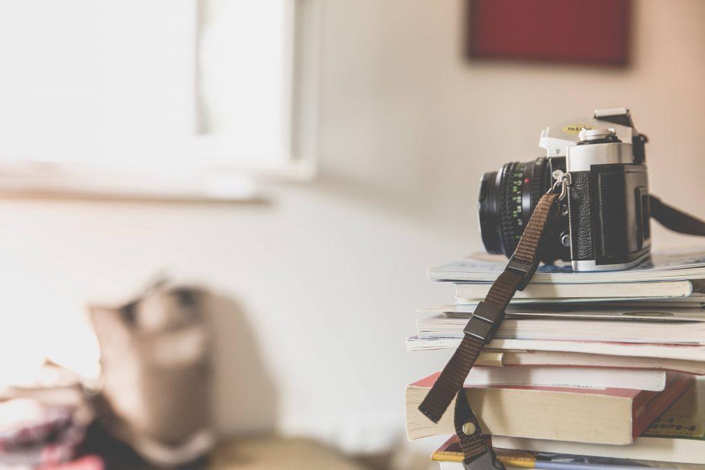 Black Bridge Camera on Top of Piled Books Wallpaper