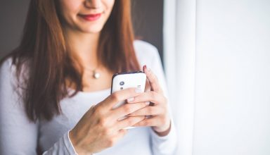 Close-up Portrait of Young Woman Typing a Message on Mobile