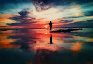 Living The Dream Standing Arms Open at Sea Shore Wallpaper