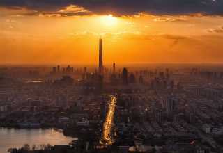 Tall Buildings Tower Sun in Clouds Lake Cityscape Wallpaper