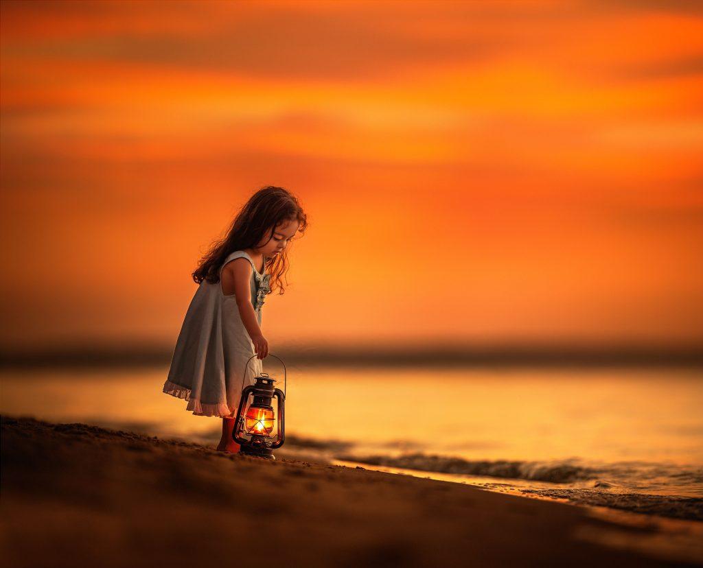 Little Girl on Beach Near Shutdown With Her Lantern Wallpaper