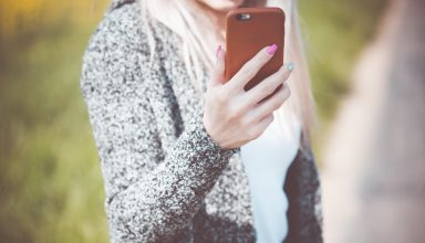 Young Woman Holding Her Iphone in Leather Case Wallpaper